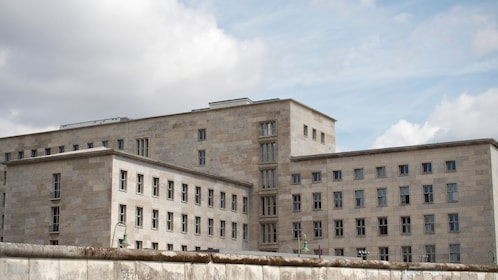 A drab gray building standing behind the Berlin wall