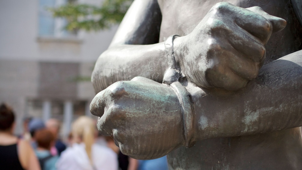 Show item 1 of 5. Detail of a bronze statue of a person with bound wrists in Berlin