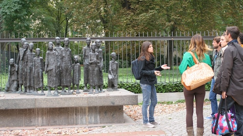 Tour group infront of a bronze memorial sculpture in a park in Berlin