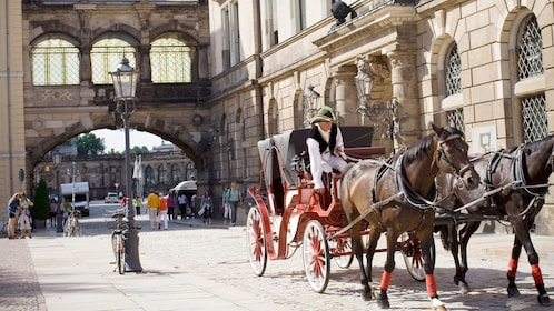 A horse drawn carriage making its way down a cobblestone street in dresden
