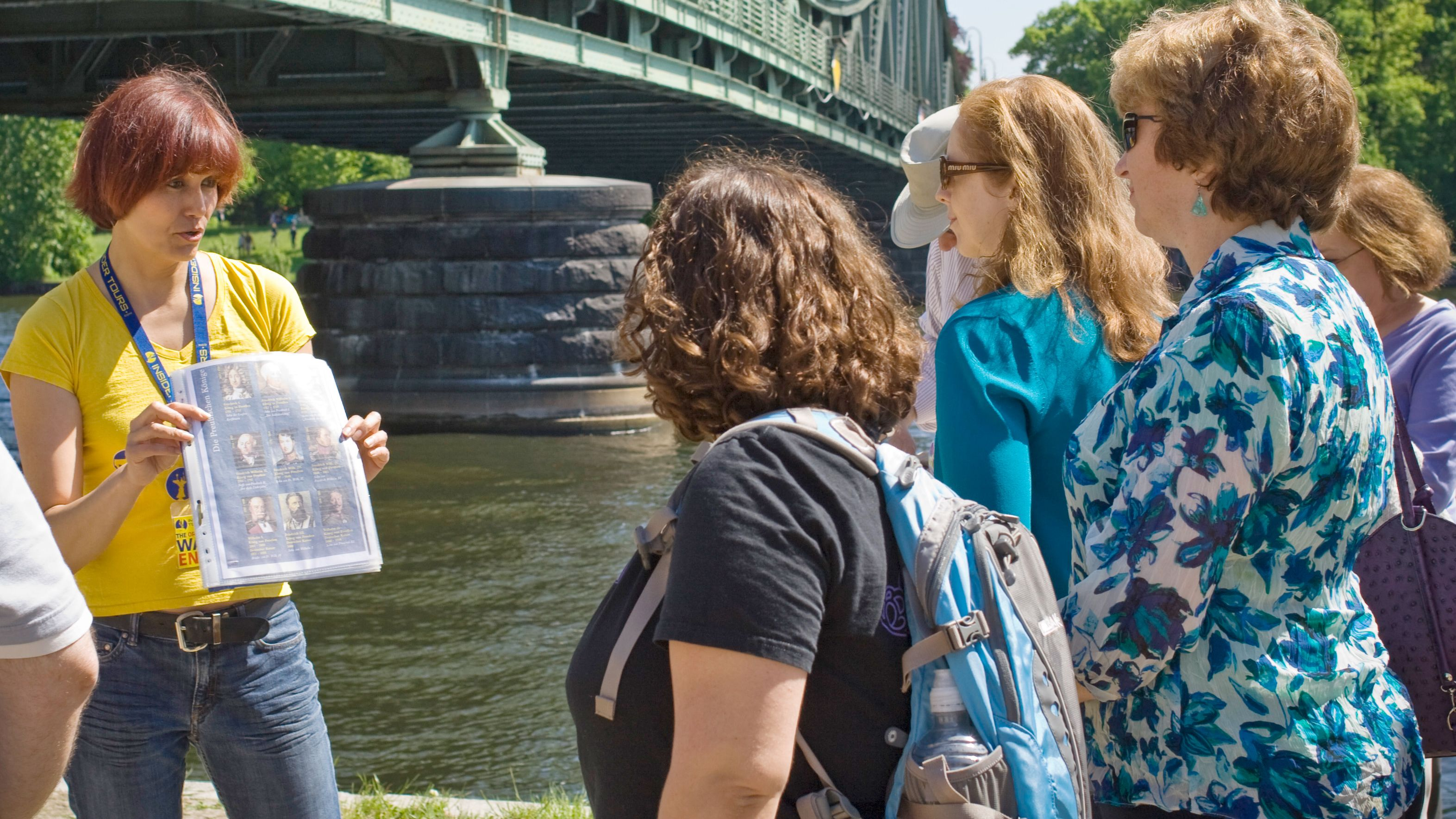 Tour guide talking to group by river in Potsdam