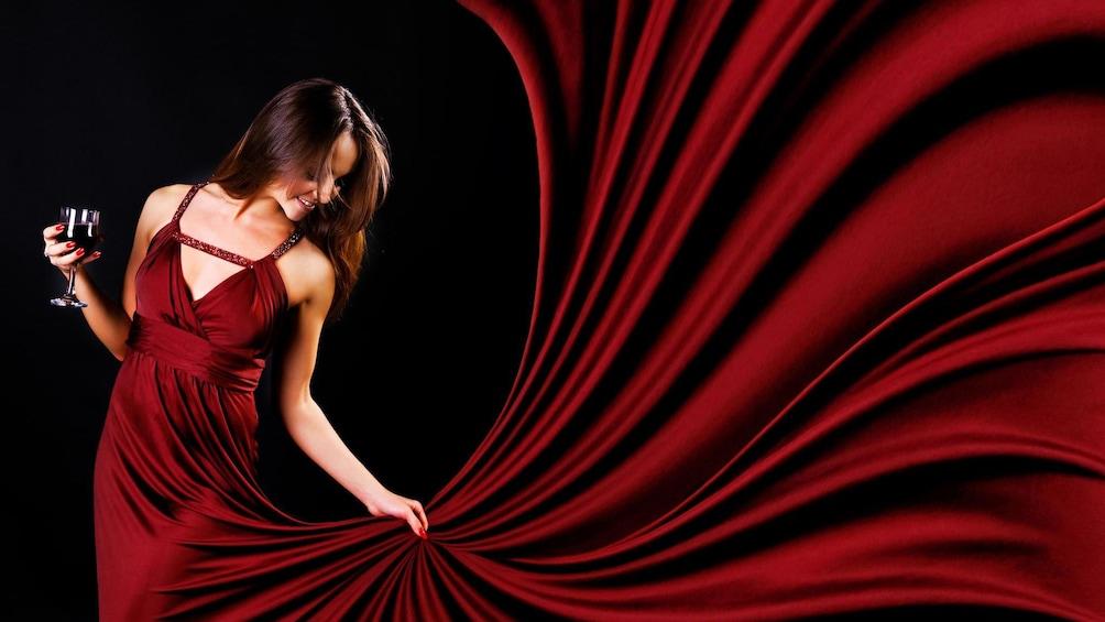 Åpne bilde 1 av 7. Woman in a red dress holding a glass of red wine