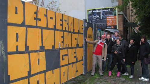 Tour group looking at a mural on a fence in Berlin