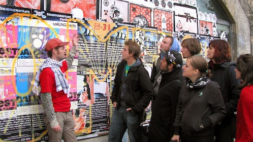 Tour group looking at a poster and graffiti covered wall in Berlin