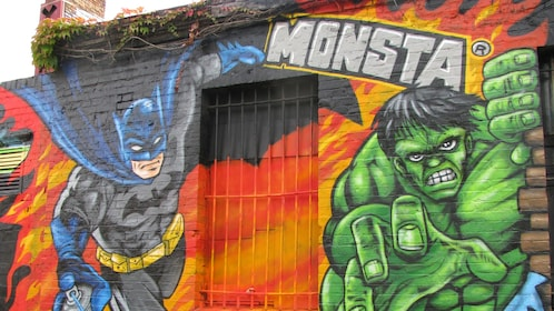 A Mural of Bat Man and the Hulk on the side of a building in Berlin