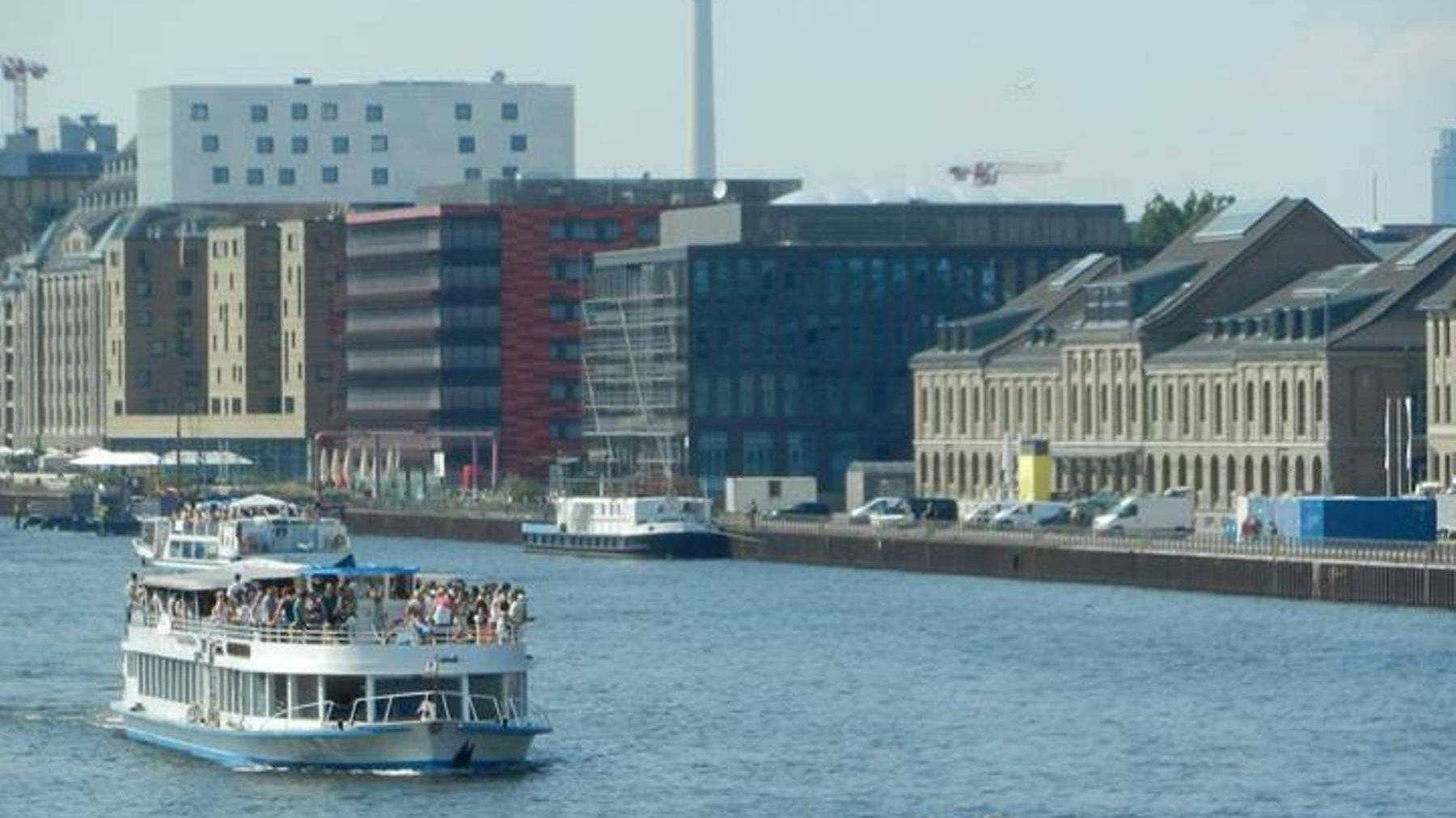 River cruise boat sailing past buildings on the banks of the Spree river in Berlin