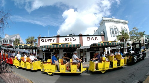 The Conch Tour Train driving along a bar in Key West