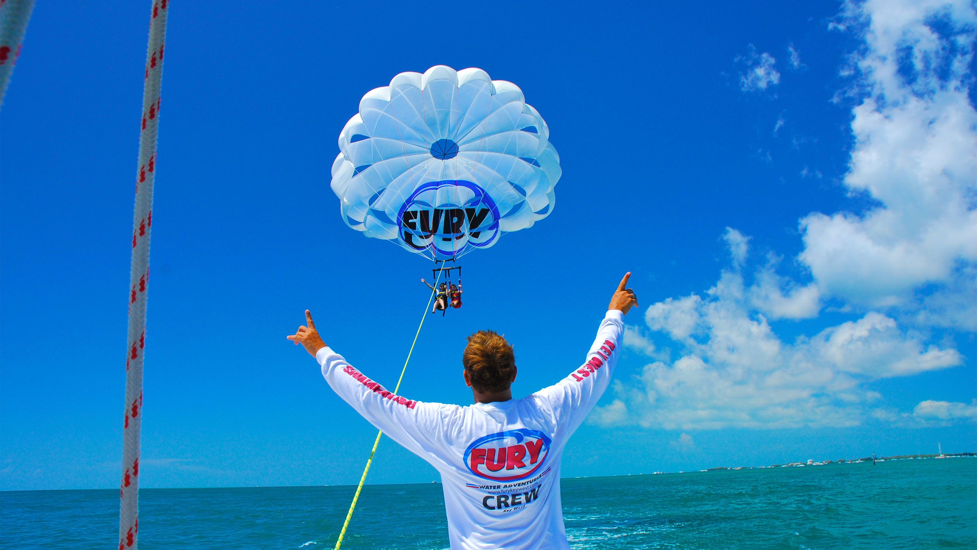 Crew member guiding mother and daughter parasailing in Key West