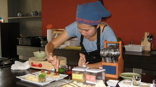 Woman plating a dish of food in Chiang Mai