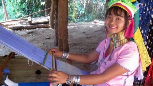 Woman working on weaving loom in chiang rai