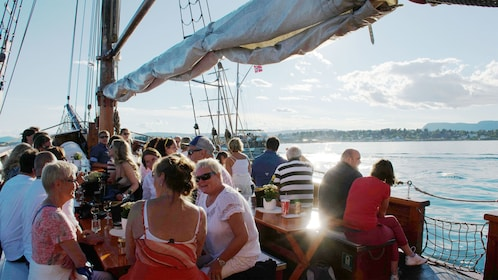 Guests enjoying drinks aboard the Summer Evening Fjord Cruise in Oslo