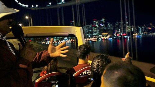 Tour guide with group on sightseeing bus at night in San Francisco