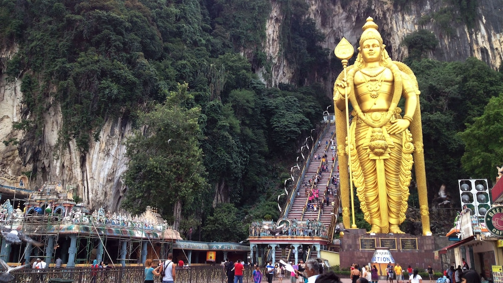 Show item 3 of 9. Large golden statue at the entrance of Batu Caves
