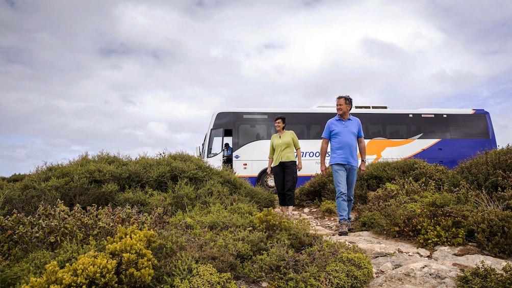 Show item 5 of 5. People walking away from a tour bus on Kangaroo Island