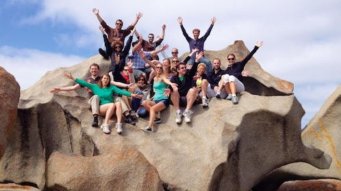 A group of people sitting on a large rock at Kangaroo Island