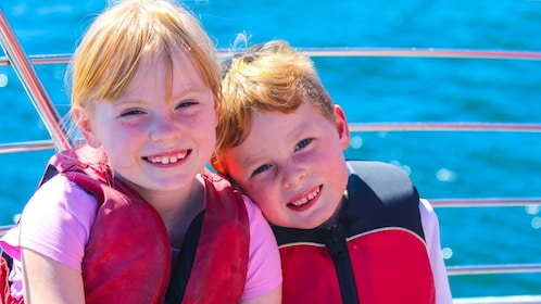 Two children in lifejackets on a whale watching boat