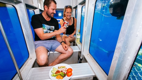 Couple having drinks and appetizers in submersible viewing cabin.