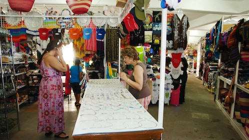 woman examines jewelry at market in Los Cabos