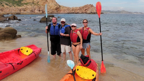 four friends standing on beach near their kayaks in Los Cabos