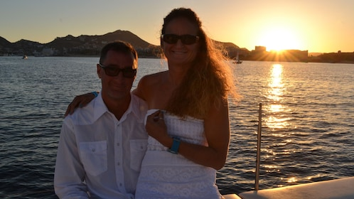 man and woman enjoying sunset on boat's deck in Los Cabos