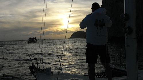passenger enjoying sunset on boat's deck in Los Cabos