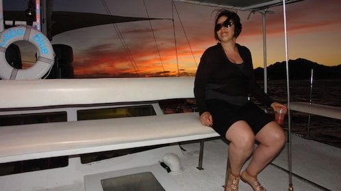 woman passenger enjoying sunset on boat's deck in Los Cabos