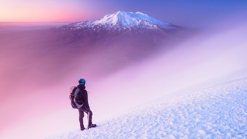 Hiker on a snowy mountain in New Zealand