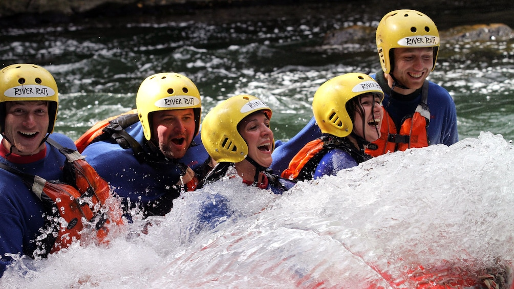 Show item 5 of 5. white water rafters partially submerged in water in New Zealand
