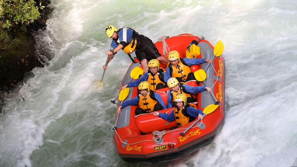 Show item 4 of 5. white water rafters hanging on while guide paddles in New Zealand