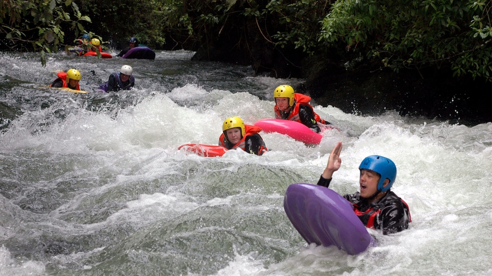 Show item 1 of 5. scattered group river sledging in New Zealand