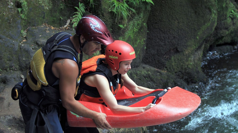 Show item 2 of 5. instructor guiding woman on river sledging in New Zealand