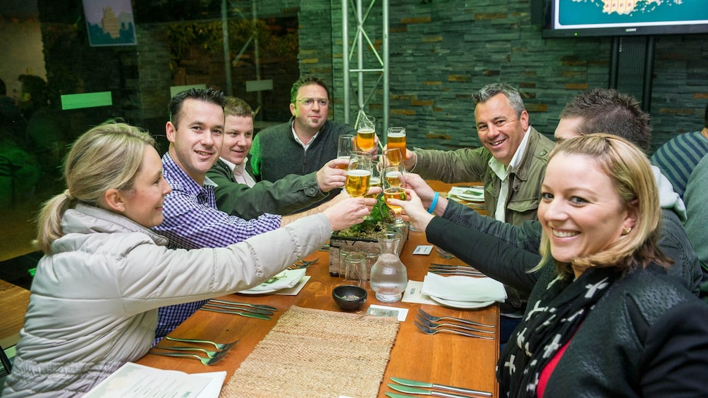 Table of guests holding beers at the Cascade Brewery Heritage Tour in Tasmania Australia