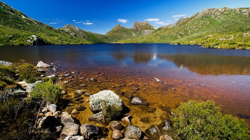 Dove Lake surrounded by green hills and Cradle Mountain in the background in Launceston