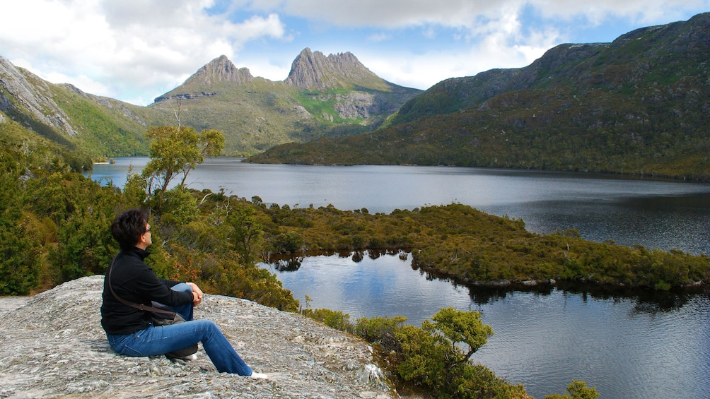 Show item 1 of 7. Man resting on a rock alongside Dove Lake looking up at Cradle Mountain in Launceston