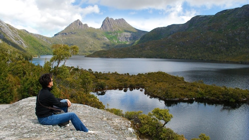 Man resting on a rock alongside Dove Lake looking up at Cradle Mountain in Launceston