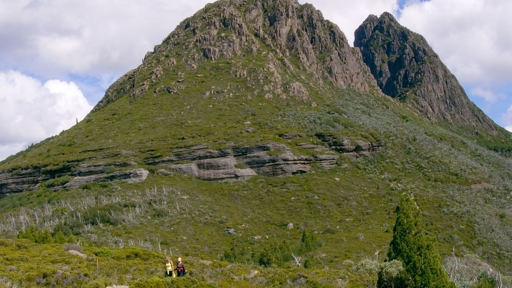 Show item 3 of 7. Hiking pair walking down a path below towards the bottom of Cradle Mountain in Launceston
