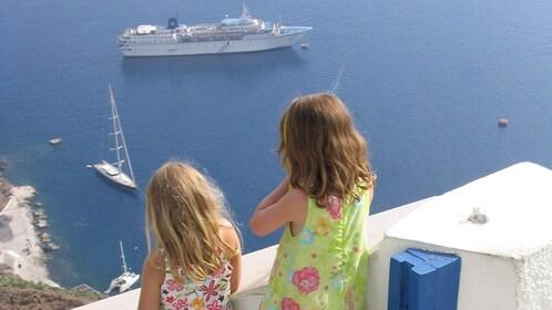 Children watching boats below in Santorini