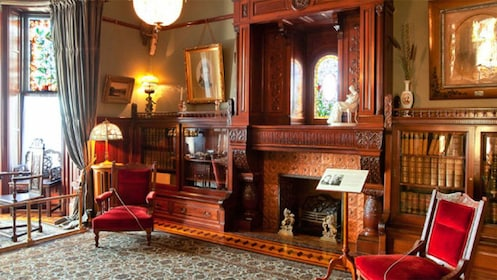 Velvet chairs on either side of a fireplace in one of the rooms of Craigdarroch Castle in Victoria