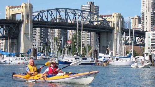 Duo kayaking near a bridge in Vancouver