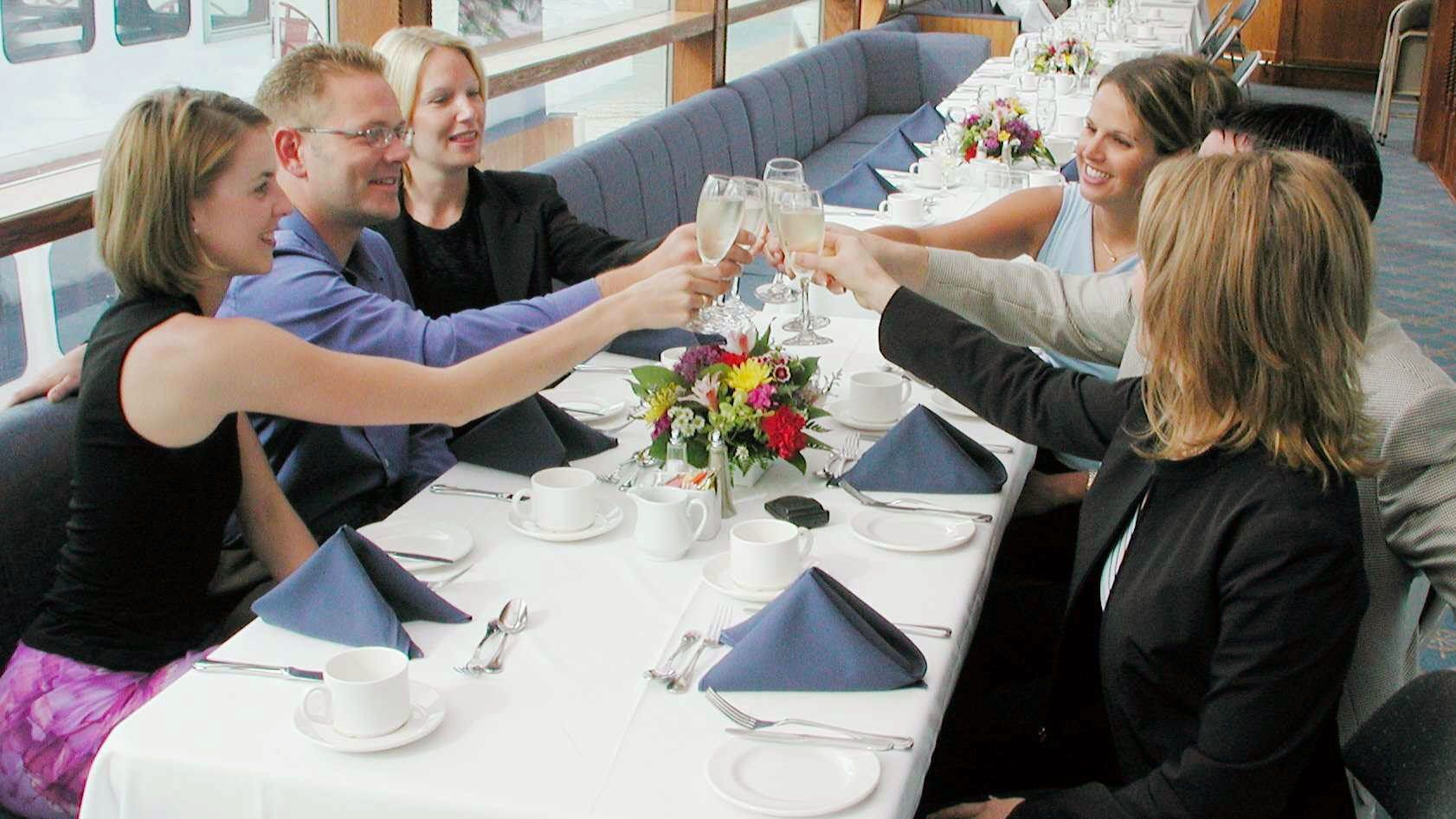 Group toasting glasses on the boat in Vancouver