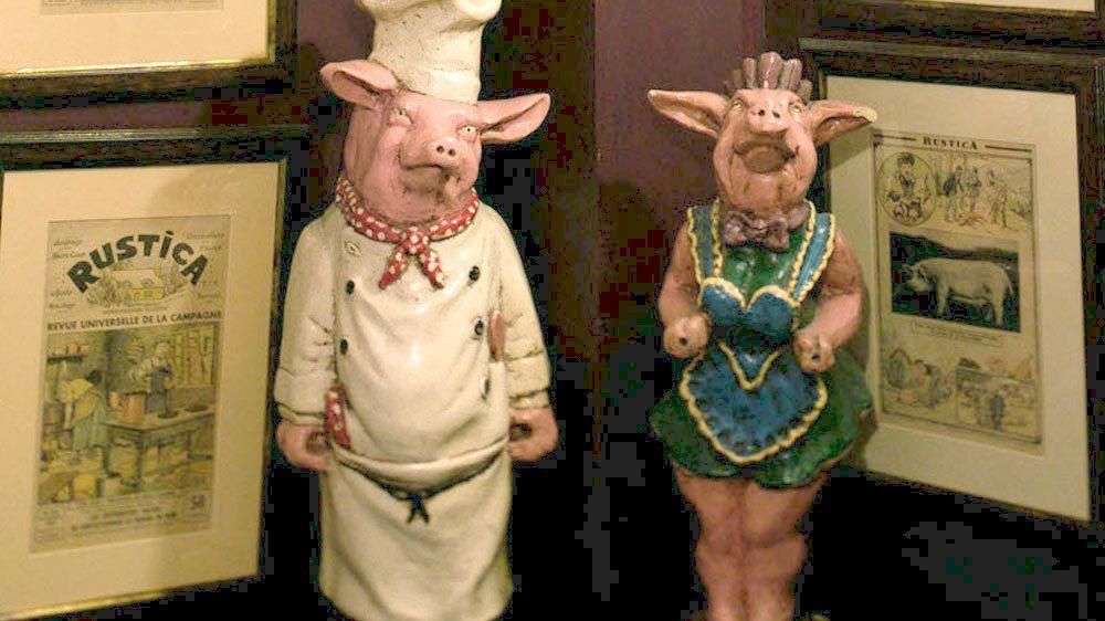 Pig statues inside Aux Trois Cochons Restaurant
