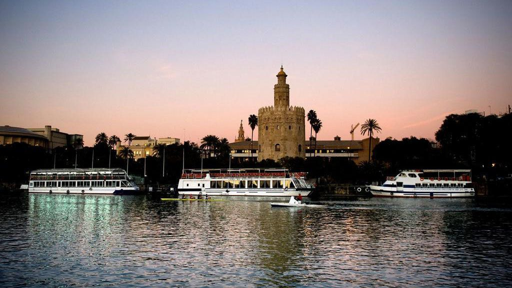 Beautiful night view of Seville on the water with boats afloat