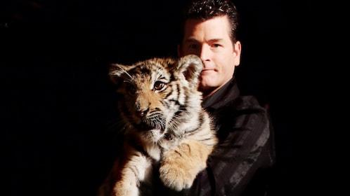 Magician Greg Frewing holding a tiger cub in Niagara Falls