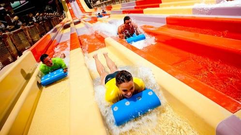 three people sliding on long water slide in Dubai