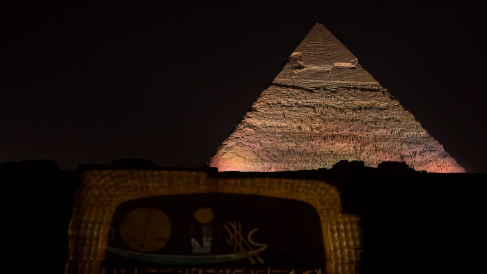 Foto 3 van 6. A pyramid lit at night in Giza