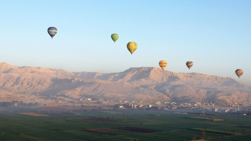 Hot air balloons over mountains in luxor
