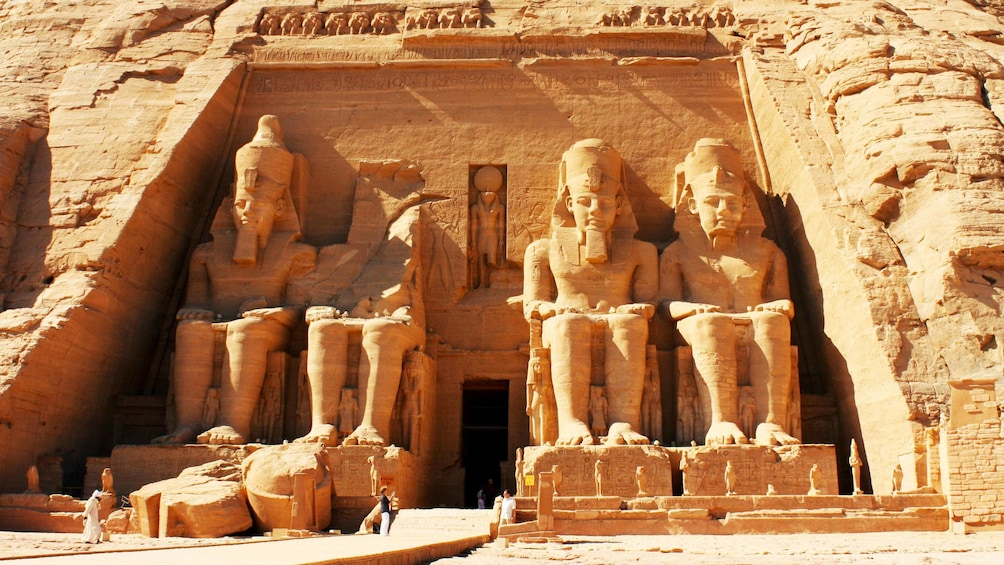 Show item 1 of 8. Tourists standing at the base of the large carved statues of Ramessess II at the Great Temple of Abu Simbel in Aswan