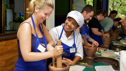 instructor helping student prepare food in Phuket
