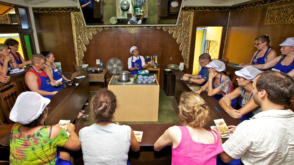 students gathered around cooking instructor in Phuket