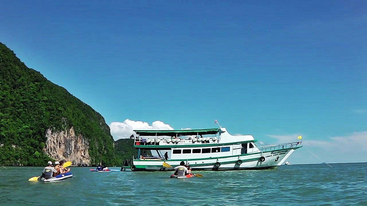 kayakimg near a boat in Phuket